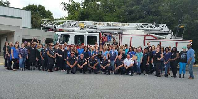 Students and staff from Paul Mitchell The School Gastonia welcome firefighters to their 9/11 Remembrance Day